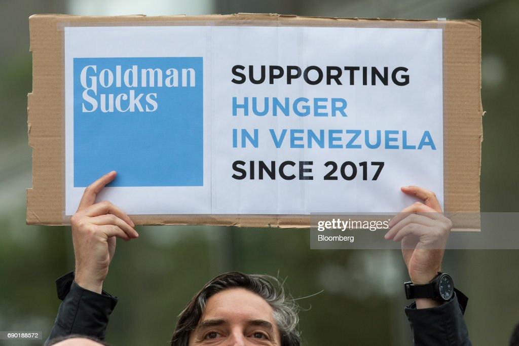 A demonstrator holds a sign during a protest outside of the Goldman Sachs Group Inc. headquarters in New York, U.S., on Tuesday, May 30, 2017. Goldman faces a probe by Venezuela's opposition leaders after buying bonds issued in 2014 by the state oil company, a purchase some lawmakers said bolsters President Nicolas Maduro as he grapples with accusations of human-rights violations. Photographer: Alexander F. Yuan/Bloomberg via Getty Images