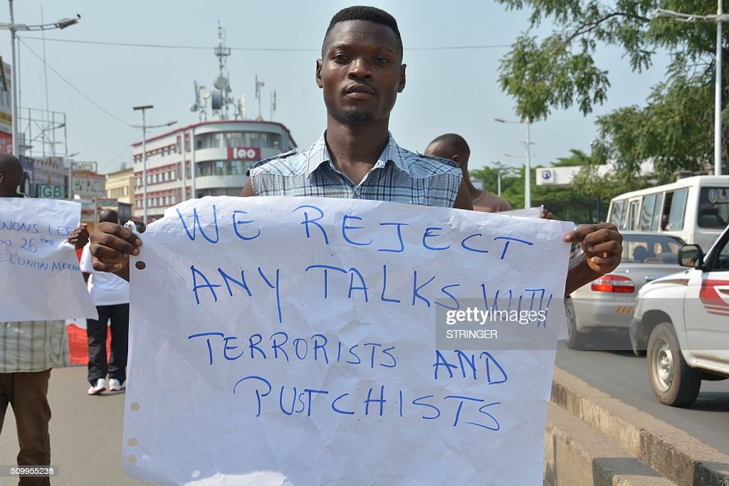 A demonstrator holds a sign on February 13, 2016 in Bujumbura during a protest against Rwanda, in front of the Rwandan embassy. Rwanda is to relocate refugees from Burundi to other countries, amid accusations Kigali was meddling in the affairs of its troubled neighbour. UN experts told the Security Council that Rwanda has recruited and trained refugees from Burundi, among them children, who wanted to remove Burundi's President Pierre Nkurunziza from power. Burundi has repeatedly accused Rwanda of backing rebels intent on overthrowing the government in Bujumbura. Kigali has fiercely denied the accusations. Burundi has been in turmoil since Nkurunziza announced plans in April to run for a third term, which he went on to win. Hundreds of people have been killed and at least 230,000 have fled the country. Some 75,000 Burundian refugees are in Rwanda, according to the UN refugee agency, UNHCR. / AFP / STRINGER