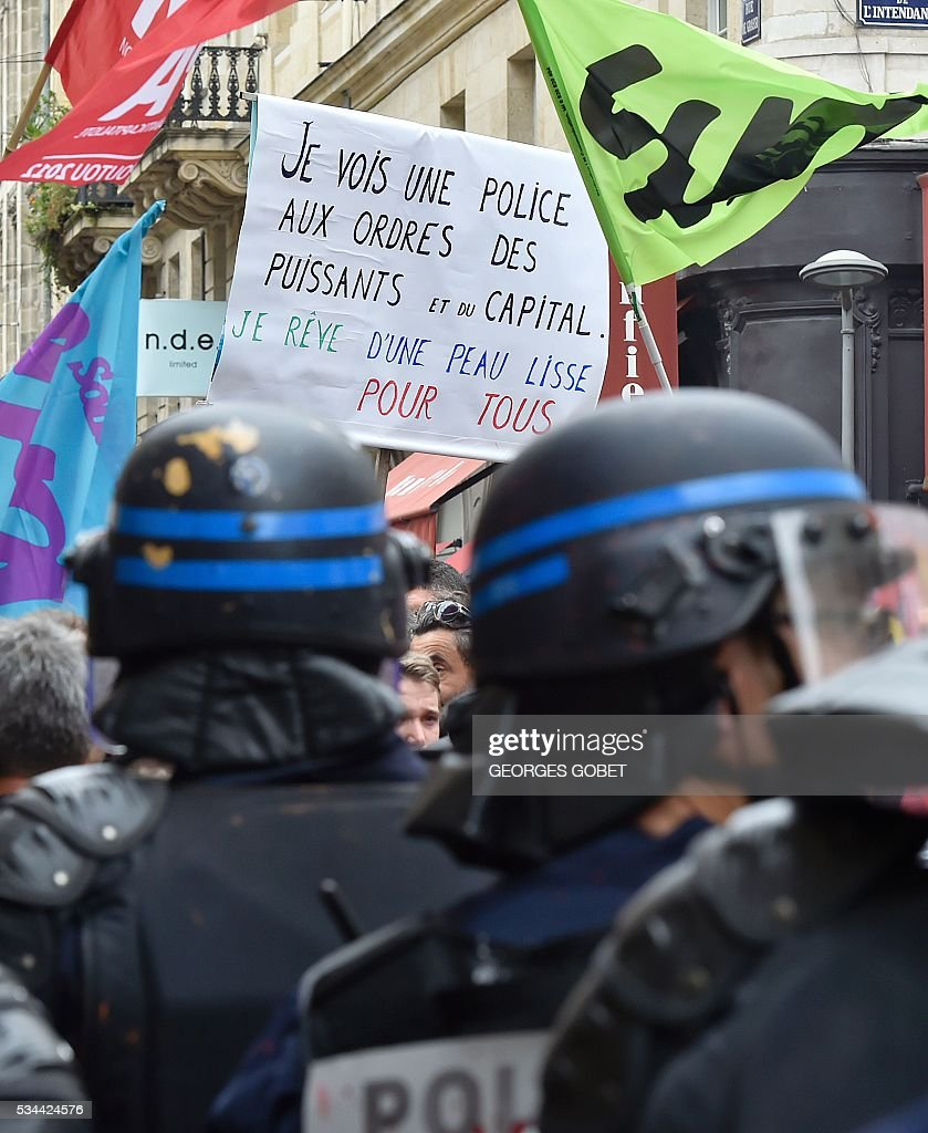 A demonstrator holds a sign reading 'I see a police force obeying to the powerful and funded' during a protest called by seven labour unions and students against the labour and employment law reform on May 26, 2016 in Bordeaux, southwest France. Fresh rallies were due to be held May 26 in Paris and other cities in the latest bout of social unrest that started three months ago and has frequently turned violent. Under intense pressure, Prime Minister Manuel Valls vowed the labour law would not be withdrawn, but said it might still be possible to make 'changes' or 'improvements'. / AFP / GEORGES