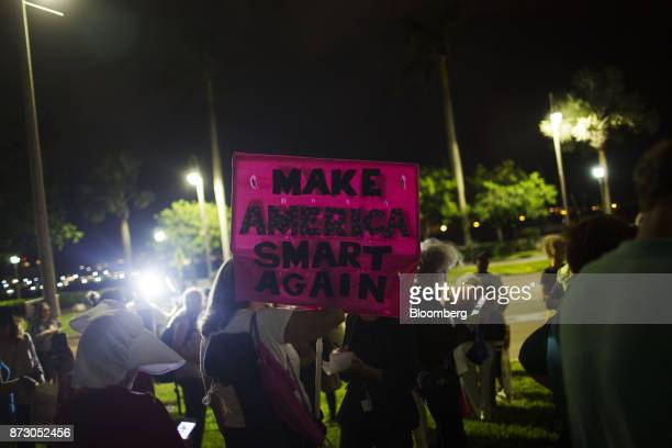 A demonstrator holds a sign reading 'Make America Smart Again' during a protest on the one year anniversary of the first antiTrump rally in West Palm...