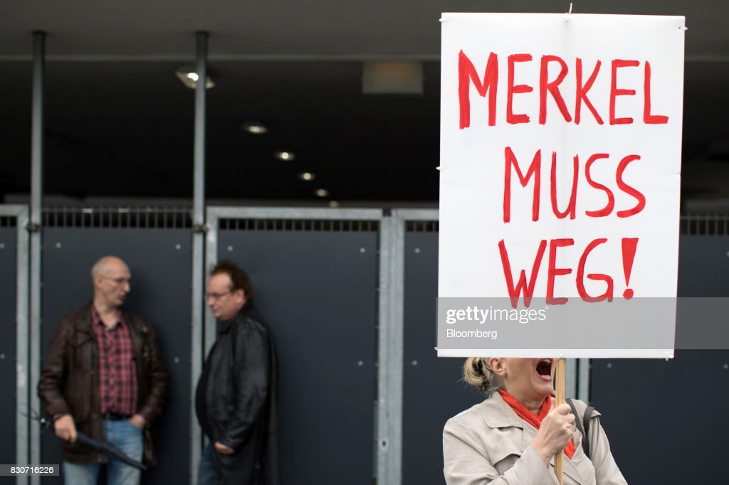 A demonstrator holds a sign reading 'Merkel Muss Weg' or 'Merkel Must Go' outside the building where a Christian Democratic Union (CDU) campaign event takes place in Dortmund, Germany, on Saturday, Aug. 12, 2017. Angela Merkel, Germany's chancellor and leader of the Christian Democratic Union (CDU), opened her re-election campaign with criticism of the nations auto executives, saying they need to embrace new technology more quickly to protect jobs and repair damage done by adiesel cheating scandal. Photographer: Jasper Juinen/Bloomberg via Getty Images