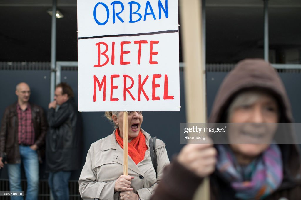 A demonstrator holds a sign reading 'Searching Orban, Offering Merkel' outside the building where a Christian Democratic Union (CDU) campaign event takes place in Dortmund, Germany, on Saturday, Aug. 12, 2017. Angela Merkel, Germany's chancellor and leader of the Christian Democratic Union (CDU), opened her re-election campaign with criticism of the nations auto executives, saying they need to embrace new technology more quickly to protect jobs and repair damage done by adiesel cheating scandal. Photographer: Jasper Juinen/Bloomberg via Getty Images
