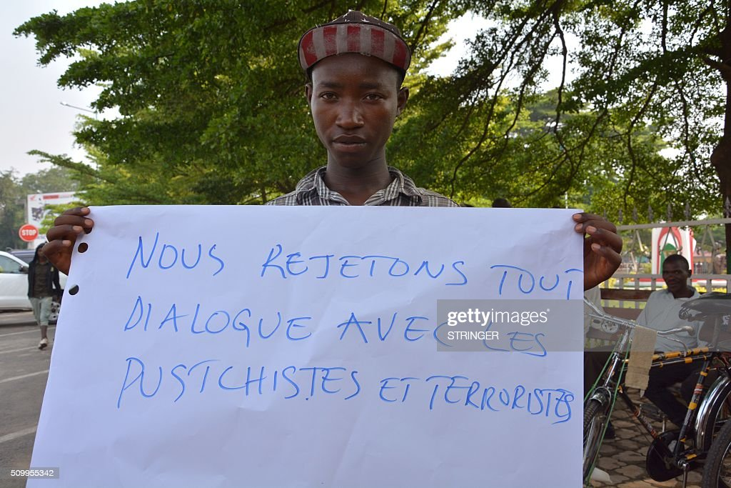 A demonstrator holds a sign reading 'we reject dialogue with putschists and terrorists' on February 13, 2016 in Bujumbura during a protest against Rwanda, in front of the Rwandan embassy. Rwanda is to relocate refugees from Burundi to other countries, amid accusations Kigali was meddling in the affairs of its troubled neighbour. UN experts told the Security Council that Rwanda has recruited and trained refugees from Burundi, among them children, who wanted to remove Burundi's President Pierre Nkurunziza from power. Burundi has repeatedly accused Rwanda of backing rebels intent on overthrowing the government in Bujumbura. Kigali has fiercely denied the accusations. Burundi has been in turmoil since Nkurunziza announced plans in April to run for a third term, which he went on to win. Hundreds of people have been killed and at least 230,000 have fled the country. Some 75,000 Burundian refugees are in Rwanda, according to the UN refugee agency, UNHCR. / AFP / STRINGER