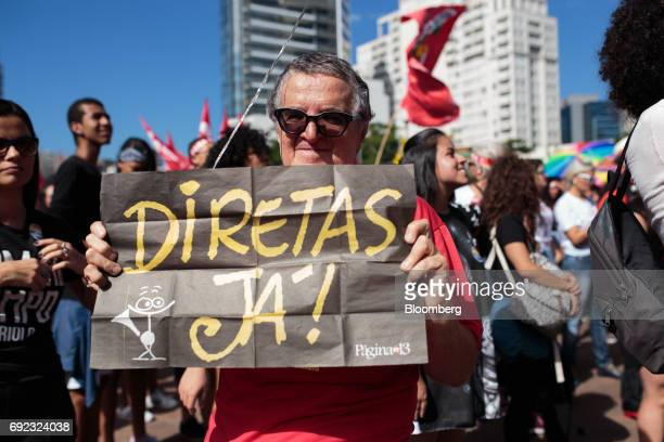 A demonstrator holds a sign that reads 'Direct Elections Now' during a protest against Brazilian President Michel Temer and government corruption at...