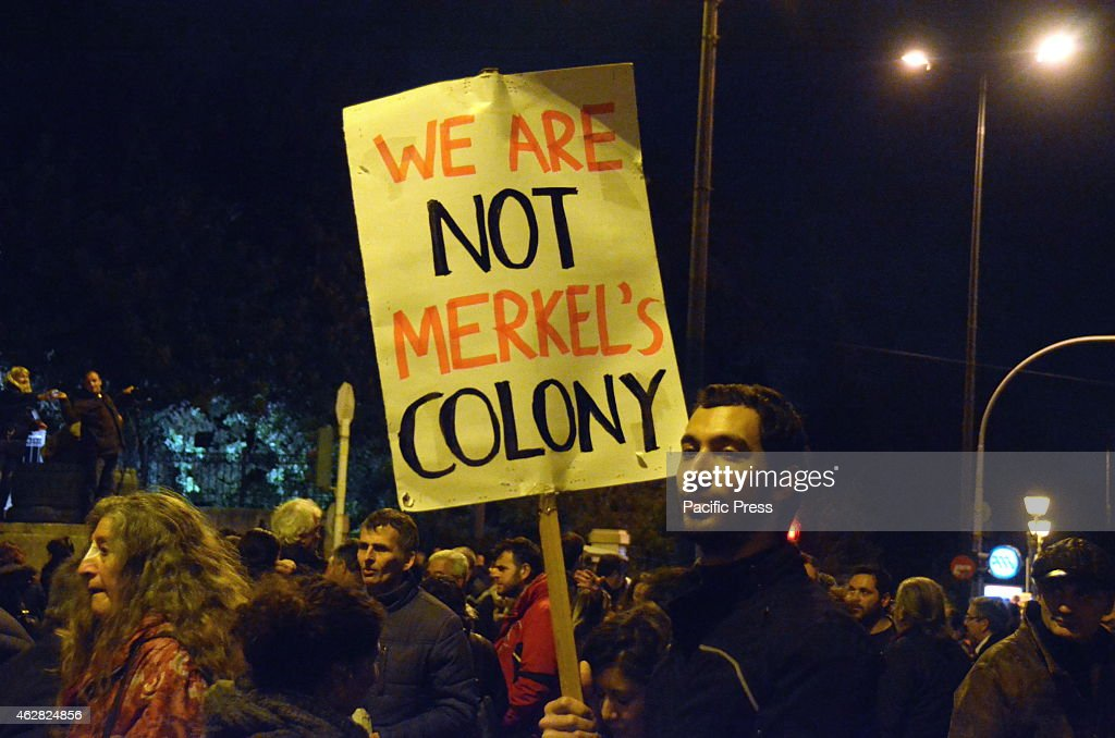 A demonstrator holds a sign that reads 'We are not Merkel's colony'.A huge demonstration was organised in Syntagma square by Greek people to show their support to the Greek goverment and its effort to stop the austerity measures despite the heavy pressure from ECB and Troika.