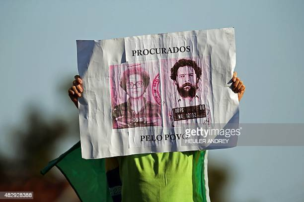 A demonstrator holds a sign with pictures of Brazilian President Dilma Rousseff and Brazilian former President Luiz Inacio Lula da Silva reading...