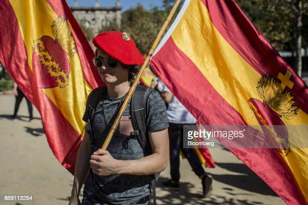 A demonstrator holds a Spanish national flag during a protest for Spanish unity in the Ciutadella Park in Barcelona Spain on Sunday Oct 8 2017...