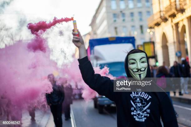 A demonstrator holds a violet smoke bomb during a rally as part of a nationwide 'Lotto Marzo' protest on the International Women's Day 2017 in Torino...