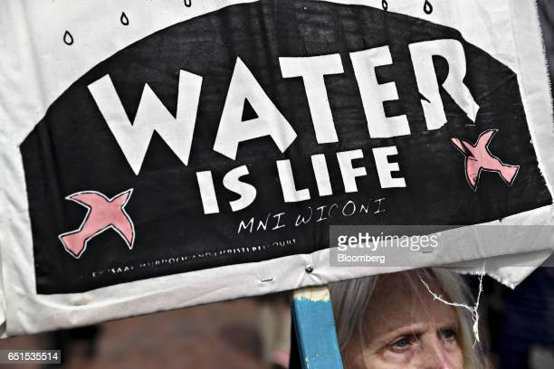 A demonstrator holds a 'Water Is Life' sign during a protest against the Dakota Access Pipeline in Washington DC US on Friday March 10 2017 The...