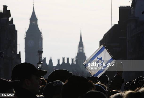 A demonstrator holds aloft an Israeli flag during a rally in Trafalgar Square in London on January 11 2009 Thousands of British Jews attended the...