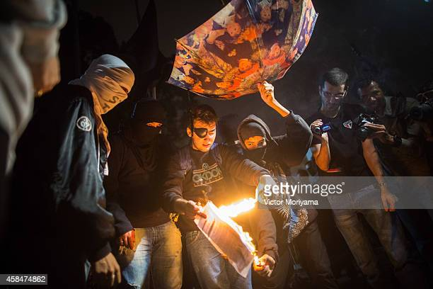 SAO PAULO BRAZIL NOVEMBER 5 A demonstrator holds an umbrella upside down to catch rainwater as another lights a paper on fire during a protest...
