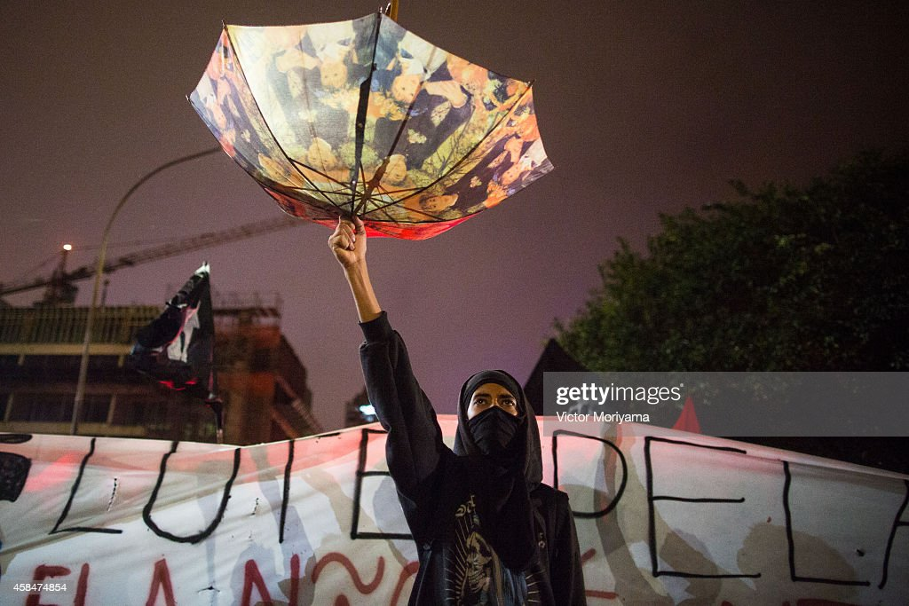 SAO PAULO BRAZIL NOVEMBER 5 A demonstrator holds an umbrella upside down to catch rainwater during a protest against the lack of water that is...