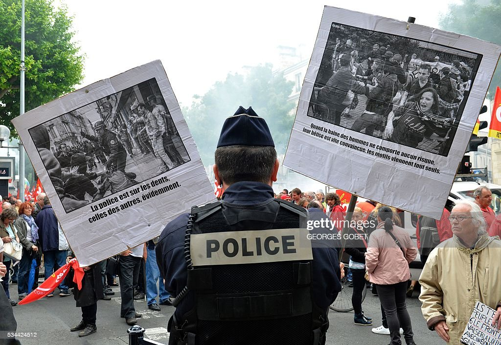 A demonstrator holds anti-police signs up to a police officer standing guard during a protest called by seven labour unions and students against labour and employment law reform on May 26, 2016 in Bordeaux, southwest France. Fresh rallies were due to be held May 26 in Paris and other cities in the latest bout of social unrest that started three months ago and has frequently turned violent. Under intense pressure, Prime Minister Manuel Valls vowed the labour law would not be withdrawn, but said it might still be possible to make 'changes' or 'improvements'. / AFP / GEORGES