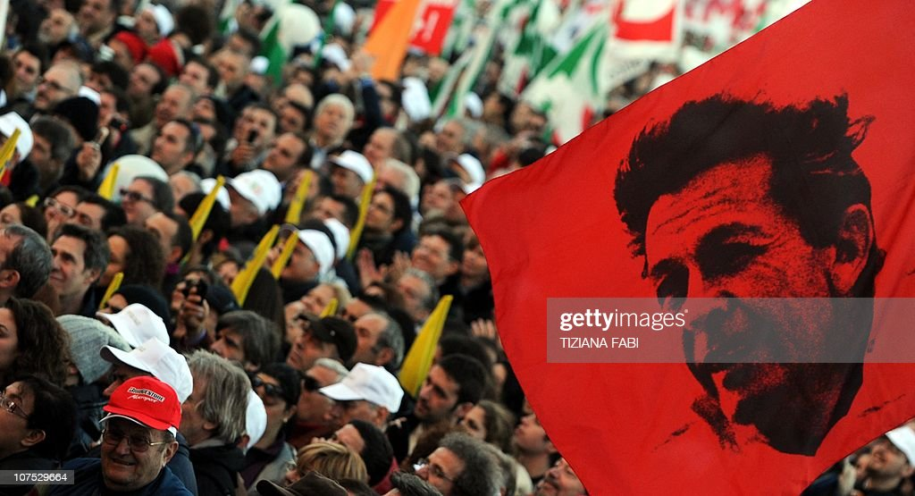A demonstrator holds flag with a portrait of Enrico Berlinguer a historic leader of Italian leftwing during a march to protest against Silvio...
