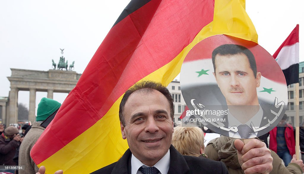 A demonstrator holds flags of Germany and a portrait of Syrian President Bashar al-Assad during a rally in front of Berlin's landmark the Brandenburg Gate to support Assad's regime on February 10, 2013 in Berlin. President Bashar al-Assad reshuffled his cabinet Saturday (February 9, 2013) as regime warplanes raided rebel areas in a bid to end the stalemate in Syria's deadly civil war and hopes for a political solution appeared to founder.