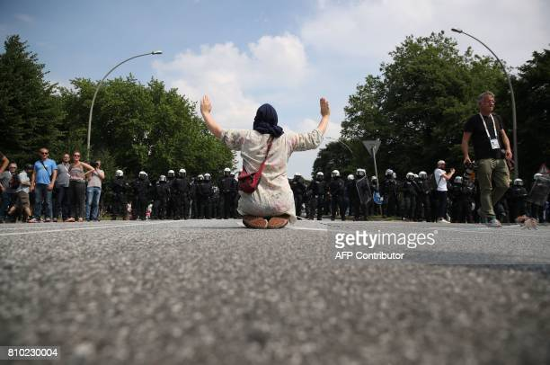 A demonstrator holds her hands up as she faces policemen during a protest on July 7 2017 in Hamburg northern Germany where leaders of the world's top...