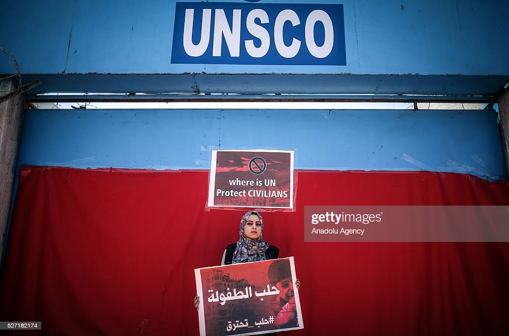 Demonstrator holds placard saying 'Aleppo is burning, do not kill children' during a protest against attacks of Assad regime and Russia to Aleppo, on May 2, 2016 in front of UNSCO office in Gaza City, Gaza.