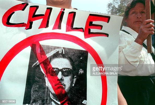 A demonstrator holds the portrait of Chilean former dictator Augusto Pinochet during a protest before the British Embassy in Lima Peru 03 November...