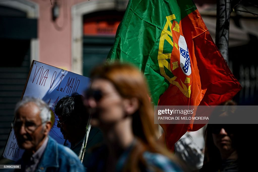 A demonstrator holds the Portuguese flag during the traditional May Day rally in Lisbon on May 1, 2016. Thousands of people demonstrated today in Lisbon and Portugal's main cities against the government's austerity measures. / AFP / PATRICIA