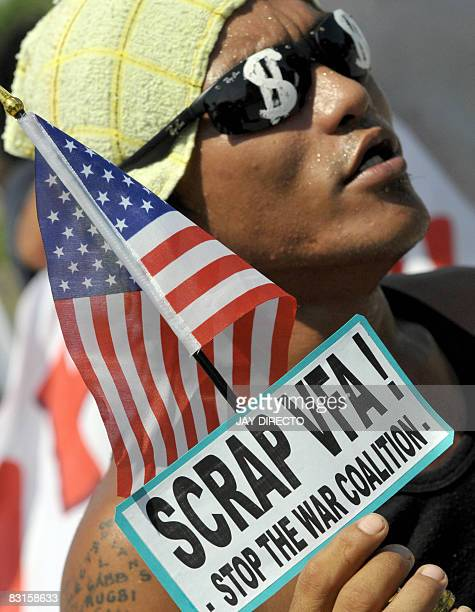 A demonstrator holds the Stars and Stripes with a banner calling for the scrapping of Visiting Forces Agreement between Philippines and US during a...