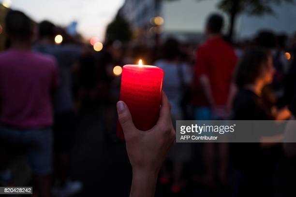 A demonstrator holds up a candle during a candlelit vigil at the site of the Polish embassy in Berlin on July 21 2017 to protest against...
