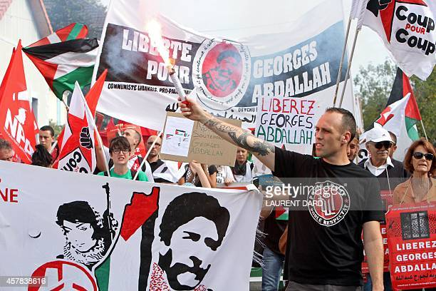 A demonstrator holds up a flare near a banner reading 'Freedom for Georges Abdallah' as around 300 people gather to call for the release of 'Lebanese...