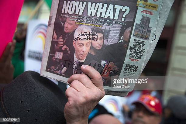 A demonstrator holds up a newspaper with a picture of Chicago Mayor Rahm Emanuel on the front during a march down State Street to protest the death...