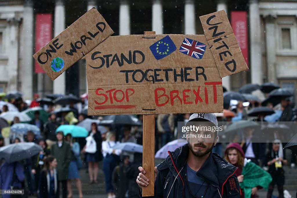 A demonstrator holds up a placard saying 'Stand together Stop Brexit' at an anti-Brexit protest in Trafalgar Square in central London on June 28, 2016. EU leaders attempted to rescue the European project and Prime Minister David Cameron sought to calm fears over Britain's vote to leave the bloc as ratings agencies downgraded the country. Britain has been pitched into uncertainty by the June 23 referendum result, with Cameron announcing his resignation, the economy facing a string of shocks and Scotland making a fresh threat to break away. / AFP / JUSTIN