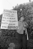 A demonstrator holds up a sign as he waits for President Nixon's arrival at the St Francis Hotel San Francisco California August 21 1969 The man's...