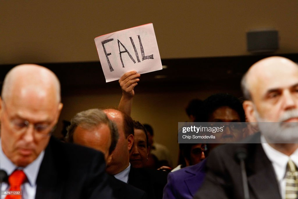A demonstrator holds up a sign behind U.S. Treasury Secretary Henry Paulson (L) and Federal Reserve Board Chairman Ben Bernanke (R) during a hearing before the Senate Banking, Housing and Urban Affairs Committee September 23, 2008 on Capitol Hill in Washington, DC. The Bush administration officials were testifying about a proposed $700 billion bailout that they hope will stabilize the faltering U.S. financial system. Many members of Congress have expressed anger at the plan they say will pay for Wall Street's mistakes at taxpayers' expense.