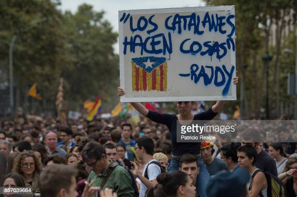 A demonstrator holds up a sign that reads a quote from the Prime Minister of Spain Mariano Rajoy 'Catalans do things' during a regional general...