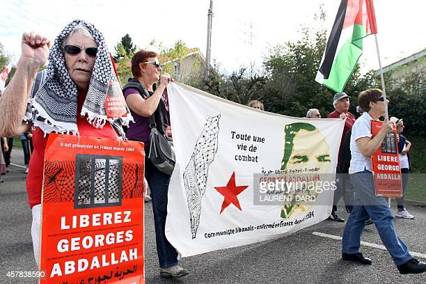 A demonstrator holds up her fist and a poster reading 'Free Georges Abdallah' as around 300 people gather to call for the release of 'Lebanese...