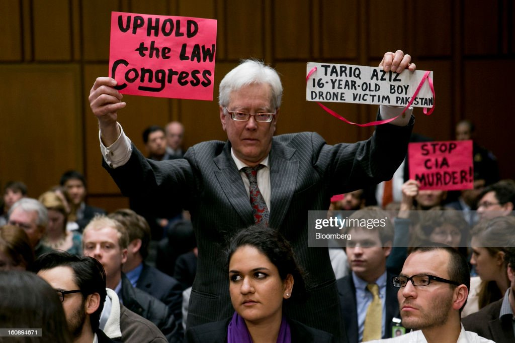 A demonstrator holds up signs in protest before a Senate Select Intelligence Committee nomination hearing of John Brennan, nominee for director of the Central Intelligence Agency (CIA) and White House chief counterterrorism adviser, in Washington, D.C., U.S., on Thursday, Feb. 7, 2013. Protesters sought to set the tone at the confirmation hearing of Brennan, President Barack Obama's nominee to lead the CIA, disrupting proceedings today before Brennan even spoke. Photographer: Andrew Harrer/Bloomberg via Getty Images