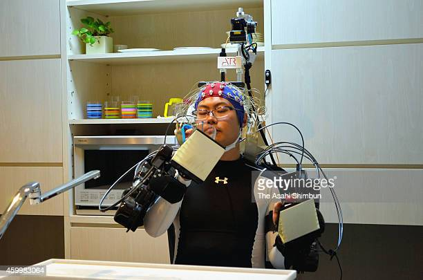 A demonstrator in a prototype wearable robotic device uses his brain waves to order the equipment to help him get a glass of water from a faucet on...