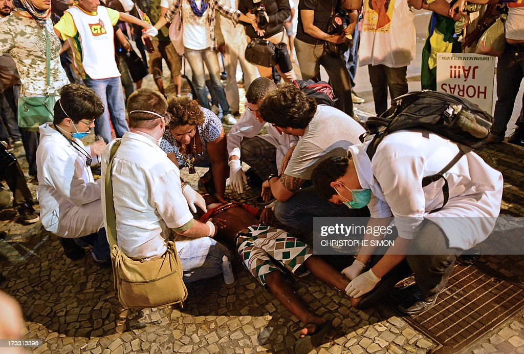 A demonstrator in assisted after being injured during clashes with the riot police which erupted following a march by Brazilian workers in Rio de Janeiro on July 11, 2013 in a day of industrial action called by major unions to press demands for better work conditions. Demonstrators on Thursday blocked roads and staged protest rallies across the country on the 'National Day of Struggles' which was called by the country's five leading labour federations during last month's mass street protests to demand better public services and an end to endemic corruption.