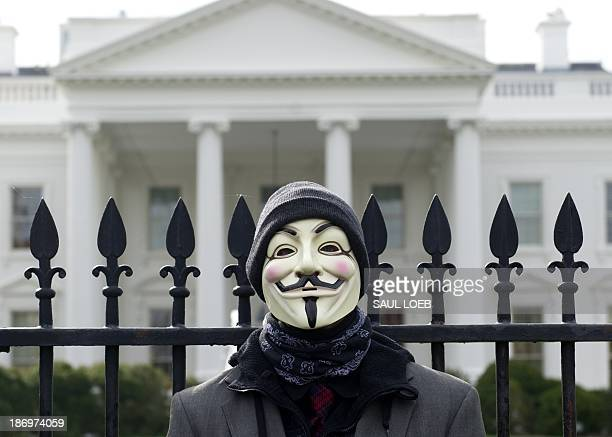 A demonstrator including supporters of the group Anonymous poses during a march in protest against corrupt governments and corporations in front of...