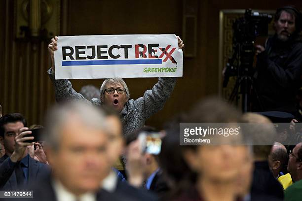 A demonstrator interrupts a Senate Foreign Relations Committee confirmation hearing for Rex Tillerson former chief executive officer of Exxon Mobil...