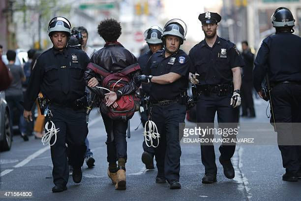 A demonstrator is arrested by police officers during a protest April 29 2015 at Union Square in New York held in solidarity with demonstrators in...