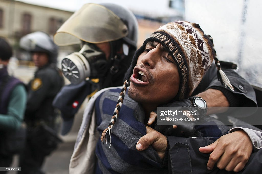 A demonstrator is arrested by the police during a students and workers protest against the government, in Lima on July 27, 2013. Students protested against a bill --that if passed-- would reduce university autonomy, whilst workers did it against a new civil service law which could bring massive dismissals, according to the workers' union. AFP PHOTO / ERNESTO BENAVIDES