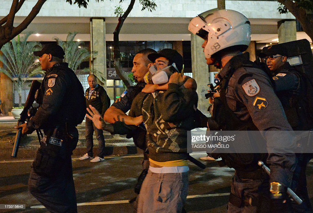 A demonstrator is arrested by the riot police during clashes which erupted after a march by Brazilian workers in Rio de Janeiro on July 11, 2013 in a day of industrial action called by major unions to press demands for better work conditions. Demonstrators on Thursday blocked roads and staged protest rallies across the country on the 'National Day of Struggles' which was called by the country's five leading labour federations during last month's mass street protests to demand better public services and an end to endemic corruption.