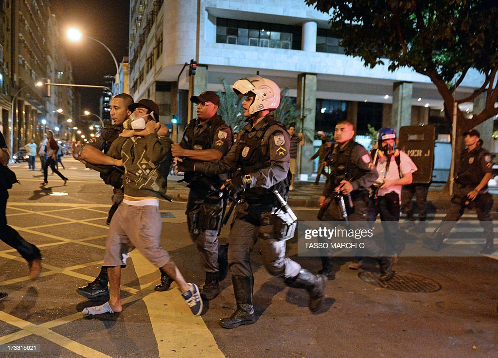 A demonstrator is arrested by the riot police in Rio de Janeiro on July 11, 2013 after clashes erupted in parts of the city following a march by Brazilian workers in a day of industrial action called by major unions to press demands for better work conditions. Demonstrators on Thursday blocked roads and staged protest rallies across the country on the 'National Day of Struggles' which was called by the country's five leading labour federations during last month's mass street protests to demand better public services and an end to endemic corruption.