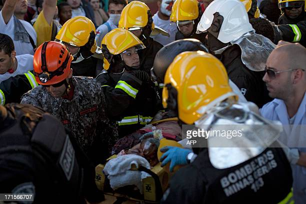 A demonstrator is assisted by firefighters after falling from the Jose Alencar viaduct during a protest outside the Mineirao stadium in Belo...