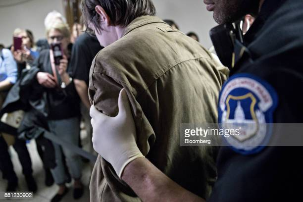 A demonstrator is detained by a US Capitol police officer after a Senate Budget Committee vote on tax reform in Washington DC US on Tuesday Nov 28...
