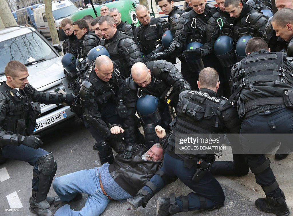 A demonstrator is detained by gendarmes as about 150 employees of French auto giant PSA Peugeot Citroen Aulnay gather outside France's MEDEF employers' association headquarters on March 28, 2013 in Paris to protest against the planned closure of their plant.