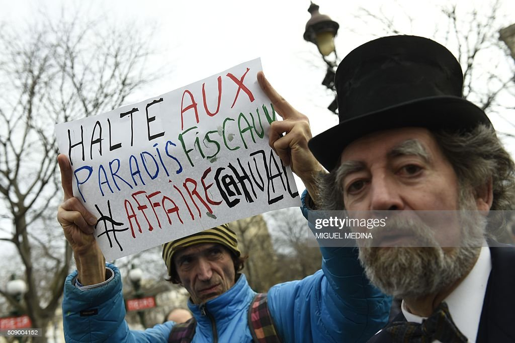 A demonstrator is dressed as a banker caricature and a demonstrator holds a sign reading 'Stop tax evasion # Cahuzac case' on February 8, 2016 in Paris during a demonstration against bank system and tax fraud, as former French budget minister Jerome Cahuzac goes on trial on February 8 for tax fraud. Cahuzac resigned in disgrace in 2013 after admitting to having a secret Swiss bank account, and faces up to seven years in jail and two million euros ($2.2 million) in fines. AFP PHOTO / MIGUEL MEDINA / AFP / MIGUEL MEDINA