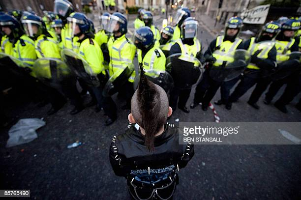 A demonstrator is pictured against a backdrop of riot police near the Bank of England in central London on April 1 2009 Violent clashes kicked off in...