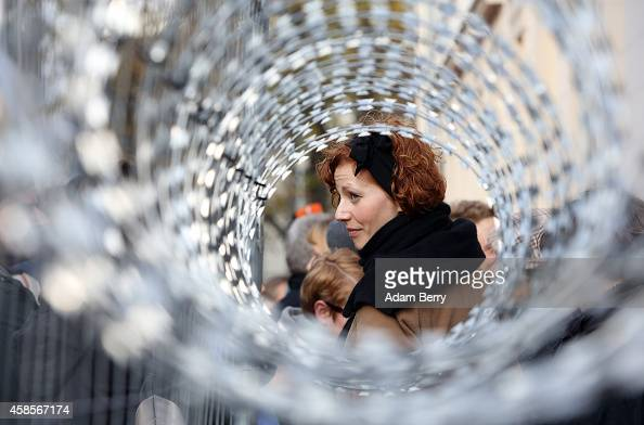 A demonstrator is seen through razor wire representing the European Union's border fence protests the German and European governments' treatment of...