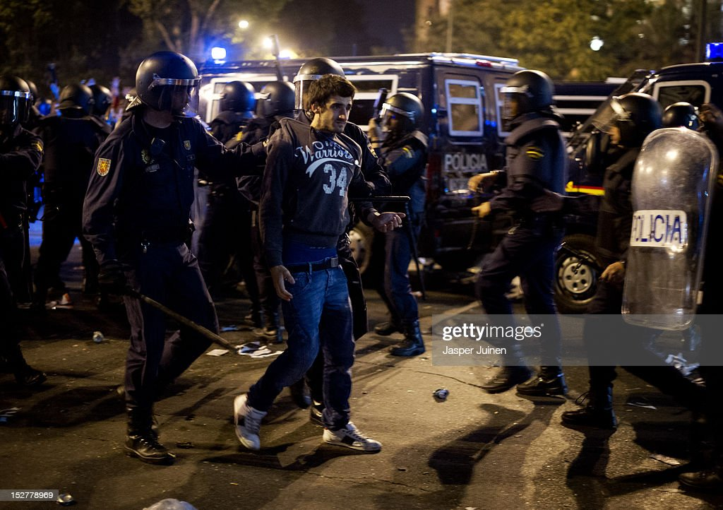 A demonstrator is taken away by a riot policeman after a protest against spending cuts and the government of Mariano Rajoy ended in riots around the Spanish parliament on September 25, 2012 in Madrid, Spain. Demonstrators from various organizations, demanding a new constitutional process, are marching today from three different locations in the center of Madrid to the lower house in the Spanish parliament.