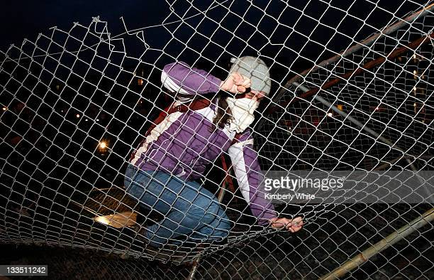 A demonstrator jumps on a chain link fence she helped to pull down November 19 2011 in Oakland California Occupy Oakland protesters calling for a...