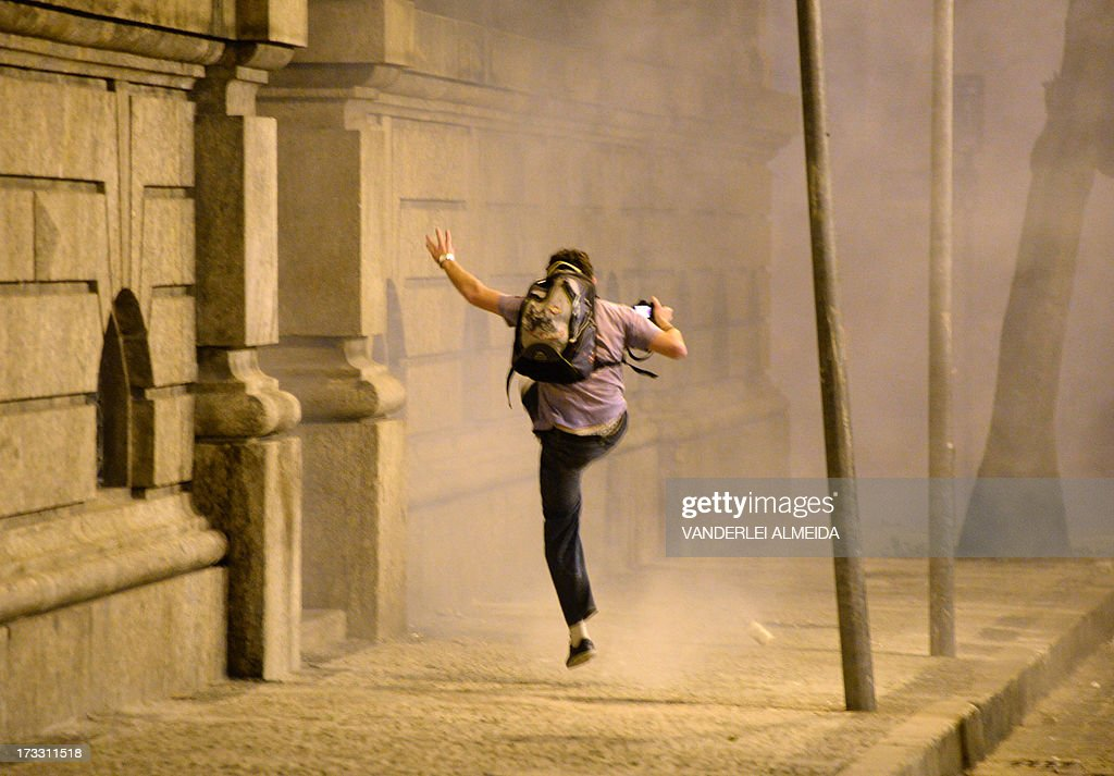 A demonstrator kicks a tear gas canister during clashes with the riot police which erupted as Brazilian workers marched in Rio de Janeiro on July 11, 2013 in a day of industrial action called by major unions to press demands for better work conditions. Demonstrators on Thursday blocked roads and staged protest rallies across the country on the 'National Day of Struggles' which was called by the country's five leading labour federations during last month's mass street protests to demand better public services and an end to endemic corruption.